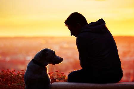 Fiatal férfi a kutyájával a napfelkeltét. Stock fotó