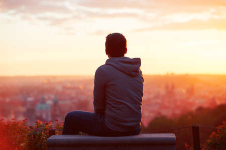 banc de parc: Jeune homme regarde le lever du soleil.