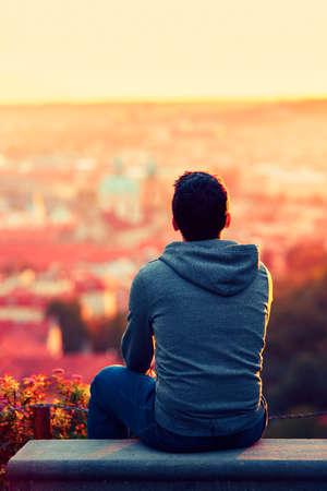 espalda: Hombre joven est� mirando la salida del sol.