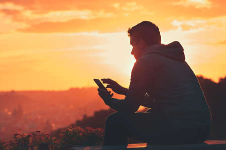 Young man with phone at the sunrise. Stockfoto