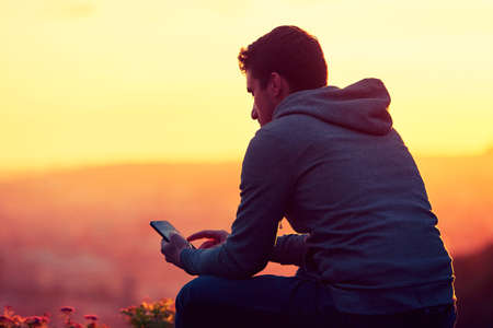 Young man with phone at the sunrise.