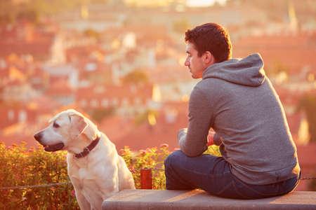 banc de parc: Jeune homme avec son chien au lever du soleil. Banque d'images