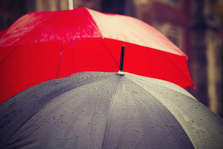 umbrella: People with umbrellas in rain on the street - selective focus