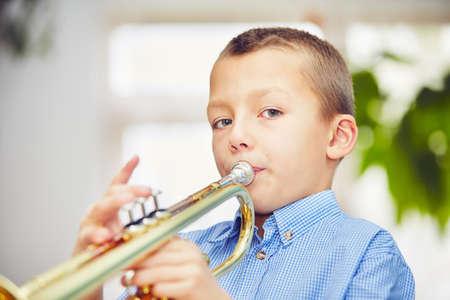 trompeta: El niño pequeño está tocando la trompeta en su casa