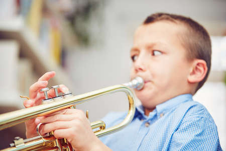 Little boy is playing the trumpet at home Stock Photo