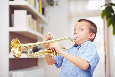 ruido: El niño pequeño está tocando la trompeta en su casa