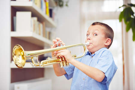 Little boy is playing the trumpet at home Zdjęcie Seryjne