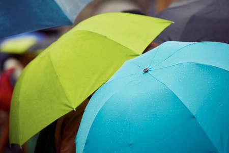 lluvia paraguas: Gente con los paraguas en la lluvia en la calle - el enfoque selectivo Foto de archivo