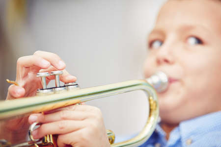 trumpeter: Little boy is playing the trumpet at home Stock Photo