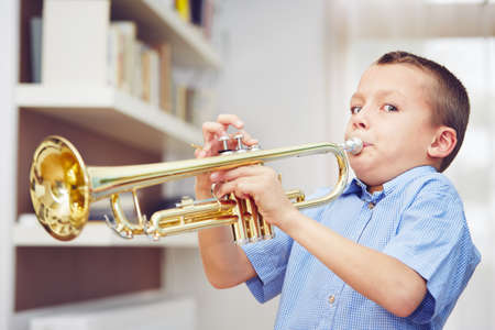 children at play: Little boy is playing the trumpet at home Stock Photo