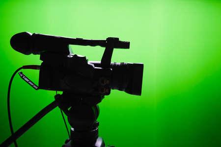 緑色の画面の前にデジタル ビデオ カメラのシルエット
