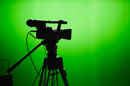 screen tv: Silhouette of digital video camera in front of the green screen