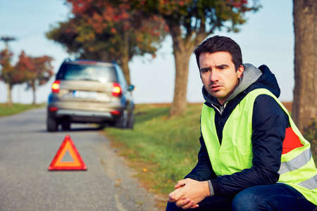 safety vest: Sad man having car trouble on the country road.