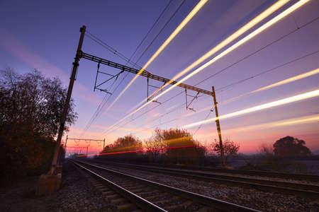 blurred motion: Passenger train on railroad tracks at the sunrise - blurred motion