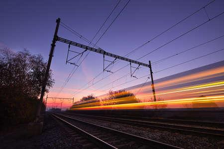 tren: Tren de pasajeros en las v�as del ferrocarril en la salida del sol - el movimiento enmascarado Foto de archivo