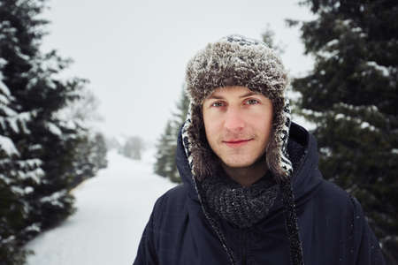 Portrait of young man outdoors in winter under snowstorm Stock Photo
