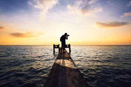 若い写真家は、日没で写真を取っています。 写真素材