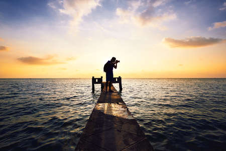 Young photographer is taking photos at the sunset.