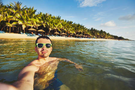 adult vietnam: Young man on vacation taking selfie in the sea. Stock Photo