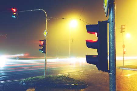 cruce de caminos: Semáforos - cruce de caminos en la noche de niebla Foto de archivo