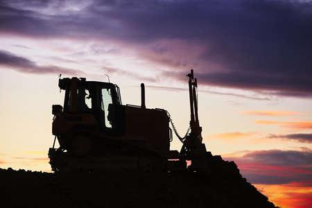 earthmover: Silhouette of the bulldozer in the building site