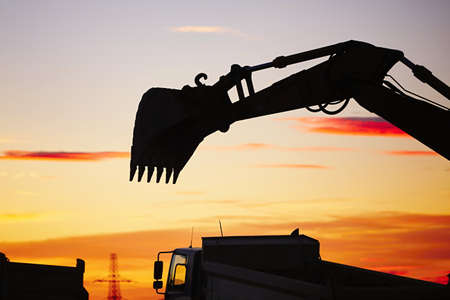 industry moody: Silhouette of the backhoe in the building site