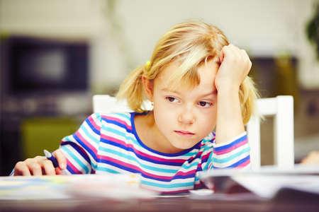 niña pensando: La niña está haciendo su tarea para la escuela primaria.
