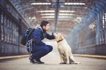 Az ember az ő sárga labrador retriever a régi híd