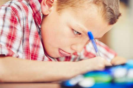 어린 소년은 초등학교에 대한 자신의 숙제를하고있다.
