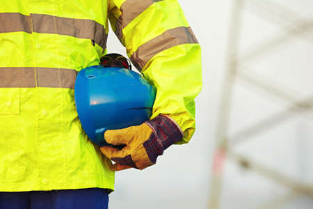 protective: Arm of worker is holding protective helmet