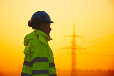 electricity substation: Worker is watching electricity pylons and substation at the sunset