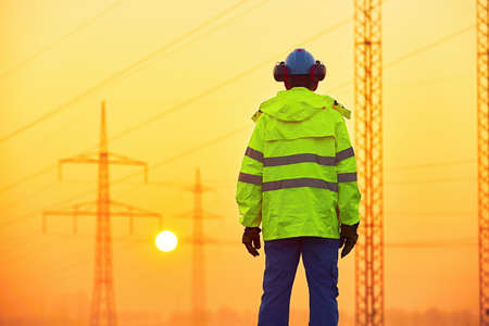 voltage: Worker is watching electricity pylons and substation at the sunrise