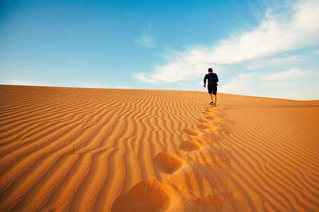 若い男は、砂漠の砂丘の上に実行しています。