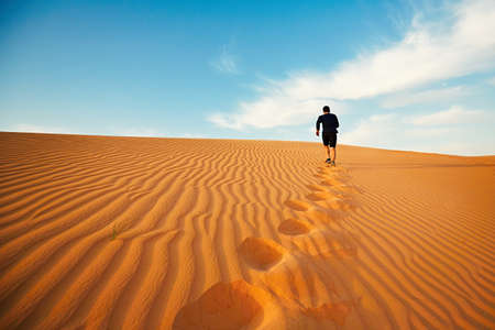 Young man is running to the top of dune in desert Stockfoto