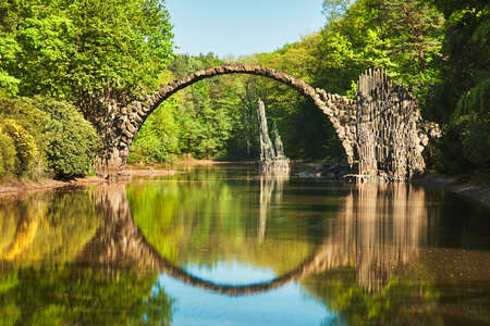 Amazing place in Germany - Rakotzbrucke also known as Devils Bridge in Kromlau. Reflection of the bridge in the water create a full circle. Stock Photo