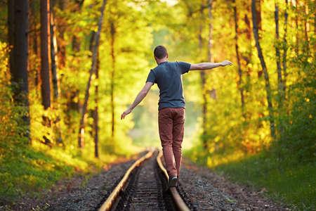 夏の時間 - 旅行で楽しんでいる若い男。夕日をフォレストで鉄道の線路の上を歩きます。