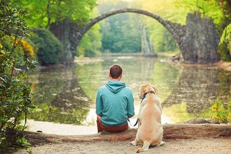 respetar: Hombre joven pensativo sentado en la orilla del estanque con un su perro - Increíble lugar en Alemania. Rakotzbrucke también conocido como Puente de los diablos en Kromlau.