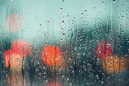 Heavy rain. Raindrop on the window of the car. Abstract blur bokeh of traffic and car light.
