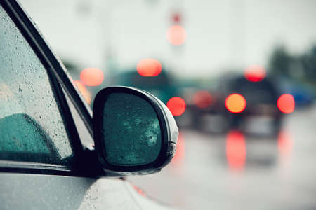 mood: Traffic in heavy rain in the city. Raindrop on the mirror of the car.