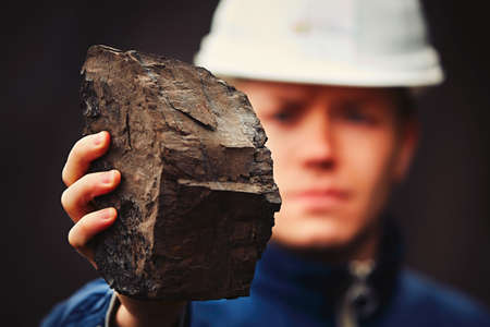 lignite: Worker is showing lignite - often referred to as brown coal Stock Photo