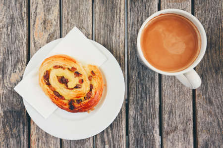 sweet pastries: Morning coffee with with sweet pastries. Top view of snack and cup of the hot drink on wooden desk. Stock Photo