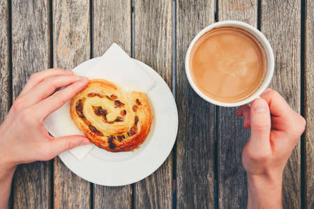 sweet pastries: Morning coffee with with sweet pastries. Breakfast of the young man. Top view of snack and hands holding cup of hot drink on wooden desk.