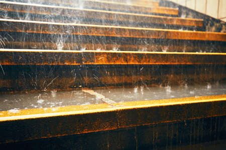 downpour: Heavy rain in the city. Rain droplets on the staircase during downpour.