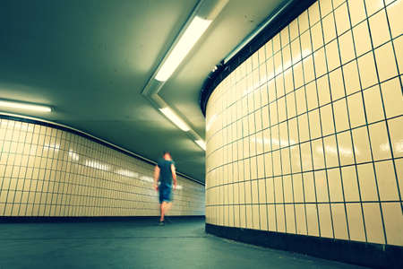 underground passage: Pedestrian is walking in underground passage from subway. Alone young man is going to the city.