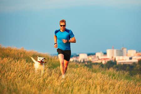 Sport Lebensstil mit Hund. Athletischer junger Mann und Labrador Retriever auf einem Hügel außerhalb der Stadt laufen. Prag, Tschechische Republik.