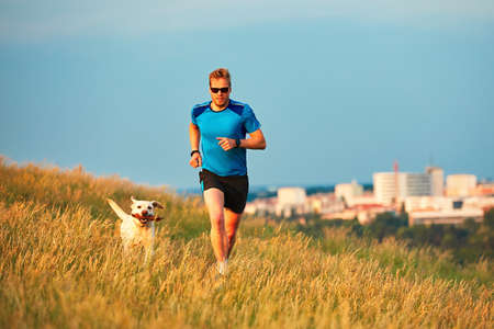 Sport lifestyle with dog. Athletic young man and labrador retriever are running on the hillside outside the city. Prague, Czech Republic.