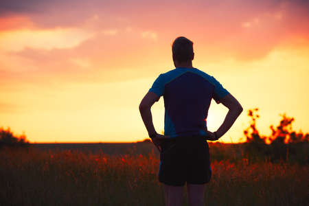 ランナーのシルエット。屋外競技ランニング。物思いにふける若い男は、自然の中に黄金の夕日の後に残りを取っています。