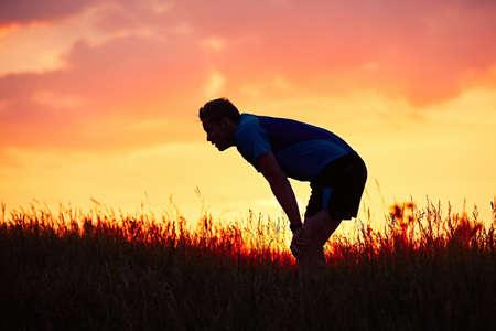 Sziluettje futó. Kültéri terepfutás. Töprengő fiatalember vesz pihenés után fut a természetben alatt arany naplemente.