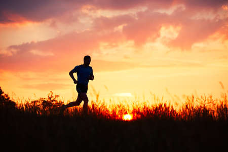 Silhouette of runner. Outdoor cross-country running. Athletic young man is running in the nature during golden sunset.