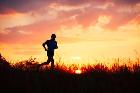 Silueta del corredor. Funcionamiento a campo al aire libre. Hombre joven atlético que se ejecuta en la naturaleza durante la puesta de sol de oro.
